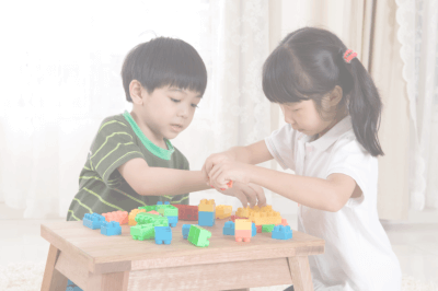 Two little kids playing lego